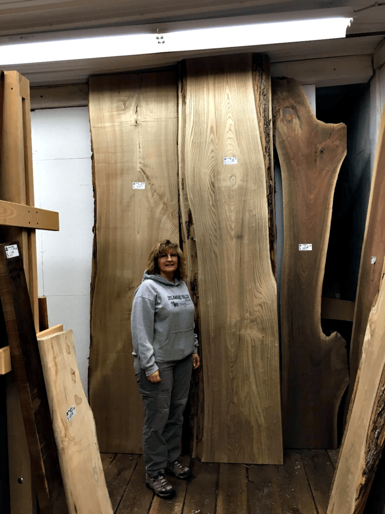 Leslie Schucker stands next to Live Edged Slabs at Bailey Wood Products